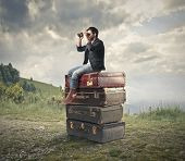 stock photo of piles  - young man sitting on a pile of vintage suitcases looking with binoculars the panorama - JPG