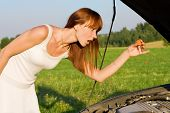 Young Woman Bent Over Car Engine