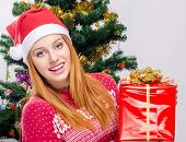 image of merry chrismas  - Girl in front of Christmas tree with gift - JPG