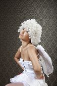 Girl in white angel costume is posing for cameras.