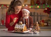 Happy Mother And Baby Decorating Christmas Cookie House In Kitch