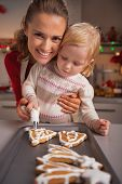 Portrait Of Happy Mother And Baby Decorating Homemade Christmas Cookies With Glaze