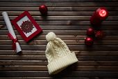 Image of red snowflake in frame, decorative toy balls, white cap, burning candle and rolled paper wrapped with red silk ribbon on wooden background