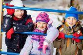 Happy kids in winterwear looking at camera outside