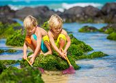 Two young boys having fun on tropical beach, happy best friends playing with fishing nets, friendshi