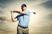Golfer at sunset, Man swinging golf club with dramatic sunset sky