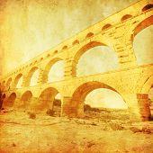 Grunge image of roman aquaduct Pont du Gard in France.