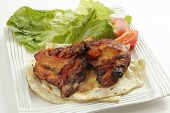 Traditional indian tandoori chicken pieces, served on flat bread with a salad and tomatoes, side vie