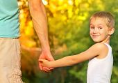 stock photo of father child  - Happy Family Father Man and Son Boy Child holding hand in hand Outdoor with summer nature on background Parents and Children relationship concept