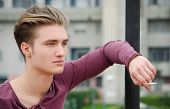 stock photo of teen smoking  - Attractive blue eyed blond young man smoking cigarette outdoors leaning against pole - JPG