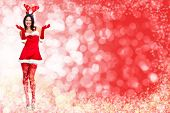 Santa helper woman over red christmas background.