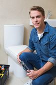 Portrait of a smiling handsome plumber with toolbox doing toilet reparation