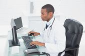 Side view of a concentrated male doctor using computer at medical office