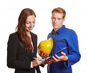 Businesswoman with construction worker signing contract on a clipboard