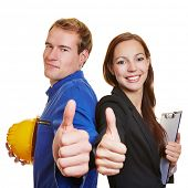 Worker and business woman holding thumbs up together and smiling