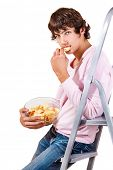 Handsome teenage male eats crisps