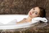 Attractive brunette woman in bath relaxing. Closeup of young woman in bathtub bathing