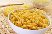 some different uncooked pasta, such as penne rigate, tagliatelle and pastina, on a table