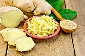 foto of ginger  - Brown dish with grated ginger a wooden spoon with powder ginger root green leaves on the wooden board