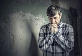 man praying on the background of old wall