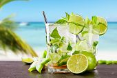 Mojito drink on wood with blur beach background