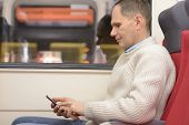 pic of passenger train  - Passenger with smartphone in a train - JPG