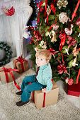 Little boy sits on big cardboard gift box near decorated Christmas tree, high angle view