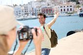 Woman taking picture of boyfriend on tourist journey