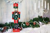 Toy Nutcracker, fir branches with cones and candlestick on mantlepiece