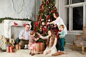 Family of five in room during decorating christmas tree