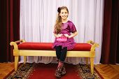 Beautiful girl in dress sits on soft bench near curtains in theatre