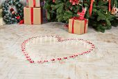 Burning tealights stand on floor in shape of heart under Christmas tree