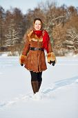 Young smiling woman dressed in sheepskin fur coat and coloured shawl goes on snow against forest on
