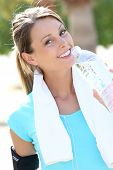 Beautiful fitness girl drinking water after exercising