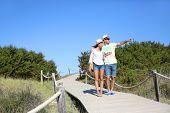 Couple walking on dunes wooden pontoon