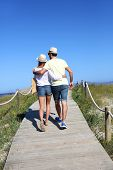 Couple walking on dunes wooden pontoon