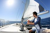 pic of sails  - Man sailing with sails out on a sunny day - JPG