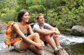 Hikers couple relaxing by river enjoying outdoor activity wearing backpacks sitting down. Woman and man hiker looking with smiling happy. Healthy lifestyle image.
