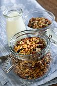 Homemade granola in open glass jar and milk or yogurt  on table with linens