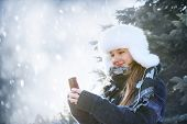 Portrait of teenage girl holding mobile phone outside in winter