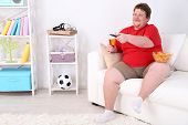pic of couch potato  - Lazy overweight male sitting on couch and watching television - JPG