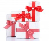 Beautiful gifts with red ribbons, isolated on white