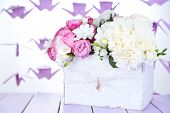 Beautiful wedding flowers in crate on table on bright background
