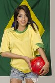 Beautiful young woman holding soccer ball wearing Brazil football colors