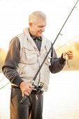 stock photo of fishermen  - Senior Fisherman holding fishing rod with fish on the hook - JPG