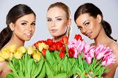 Three beautiful topless women with bunches of fresh spring tulips held to their chests smiling at th