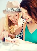 summer holidays, vacation and internet - girls looking at smartphone in cafe