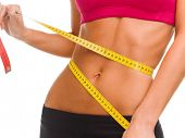 sport, fitness and diet concept - close up of trained belly with measuring tape