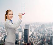 office, business and new technology concept - smiling businesswoman writing something in the air wit