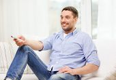 home, technology and entretainment concept - smiling man with tv remote control at home